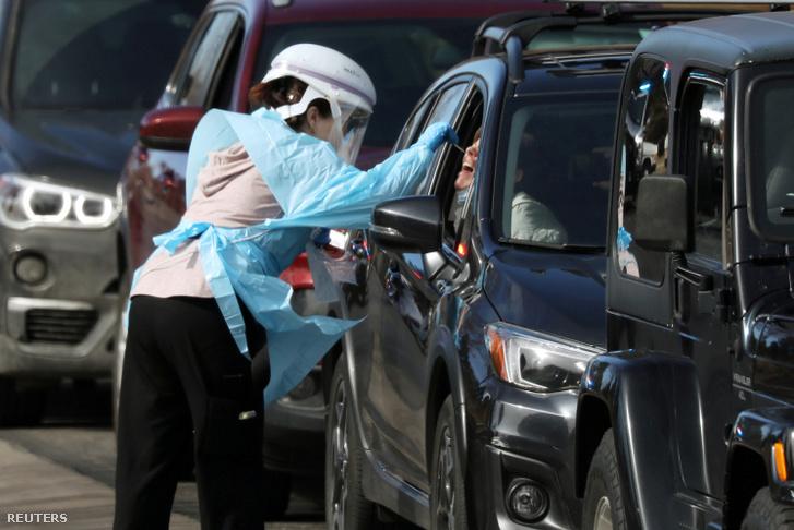 Egy egészségügyi dolgozó végez koronavírus tesztet egy autós tesztállomáson Denverben.