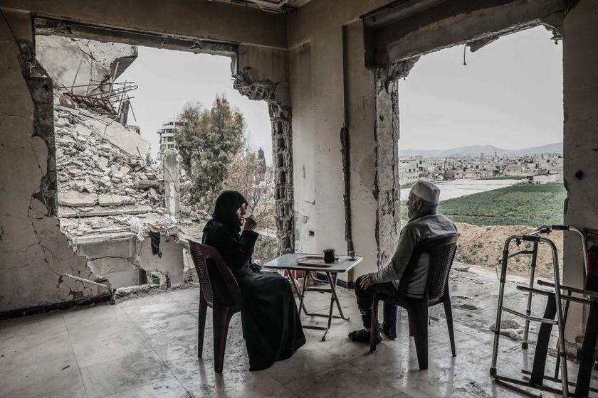 A díjnyertes fotót Sameer Al-Doumy készítette Damaszkuszban, Szíriában, ahol egy idős házaspár, Umm Mohammed és férje kávéznak a lerombolt házukban, előttük pedig a teljesen lepusztult város.