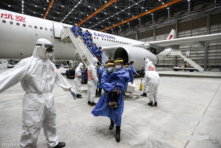 A tajvani nemzetvédelmi minisztérium által közreadott képen védőruhás katonák Vuhanból hazatérő tajvaniakat fertőtlenítenek a taojüani repülőtéren 2020. március 11-én.