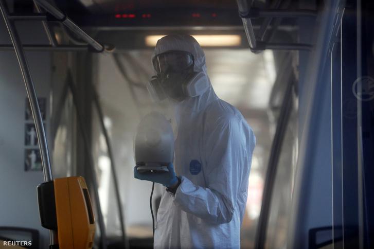 Egy védőruhában buszt fertőtlenít egy dolgozó a COVID-19 koronavírus miatt Prágában 2020. március 12-én