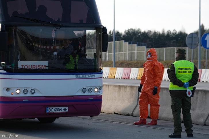 Lengyel határőrök védőfelszerelésben ellenőrzik az ország területére belépő busz utasait a cseh határnál fekvő Gorzyczkiben 2020. március 9-én