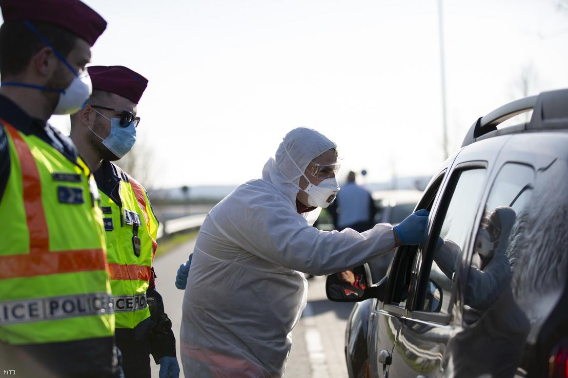 A tüdőgyulladást okozó új koronavírus-járvány miatt bevezetett határellenőrzésen rendőrök és mentő ellenőriz egy beérkező autóst a magyar-szlovén határ közelében, az M70-es autópálya csörnyeföldi pihenőhelyénél 2020. március 12-én