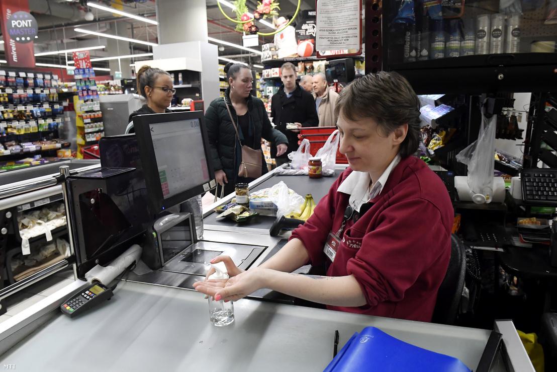 A kezét fertőtleníti egy pénztáros egy CBA Príma üzletben a Corvin bevásárlóközpontban 2020. március 11-én.
