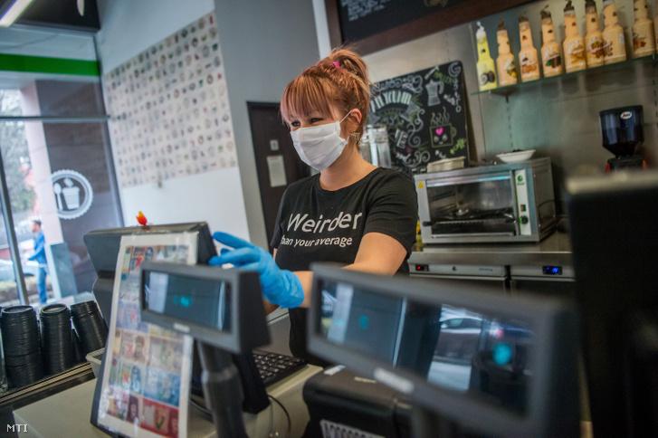 A koronavírus terjedésének megelőzése érdekében maszkban és kesztyűben dolgozik egy pénztáros a fővárosi Haller kávézóban 2020. március 11-én.