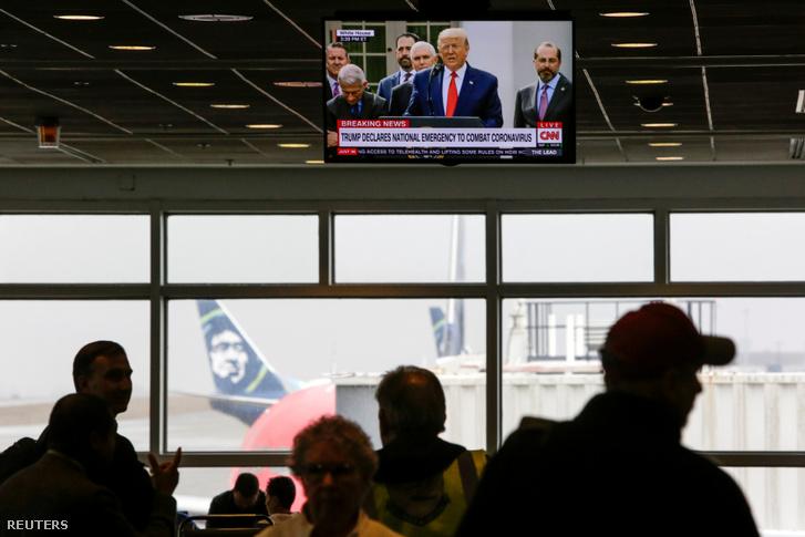 A Seattle-Tacoma repülőtér utasai figyelik egy televízión Donald Trump amerikai elnök bejelentését a szükségállapotról 2020. március 13-án.