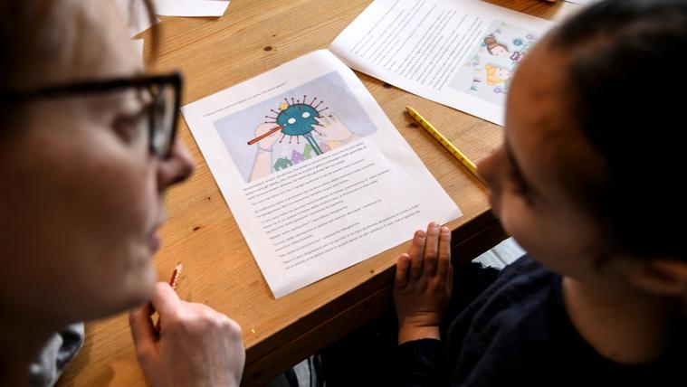 Egy anya segít az ötéves gyermekének a koronavírusról szóló házifeladat megoldásában Olaszországban 2020. március 12-én.
