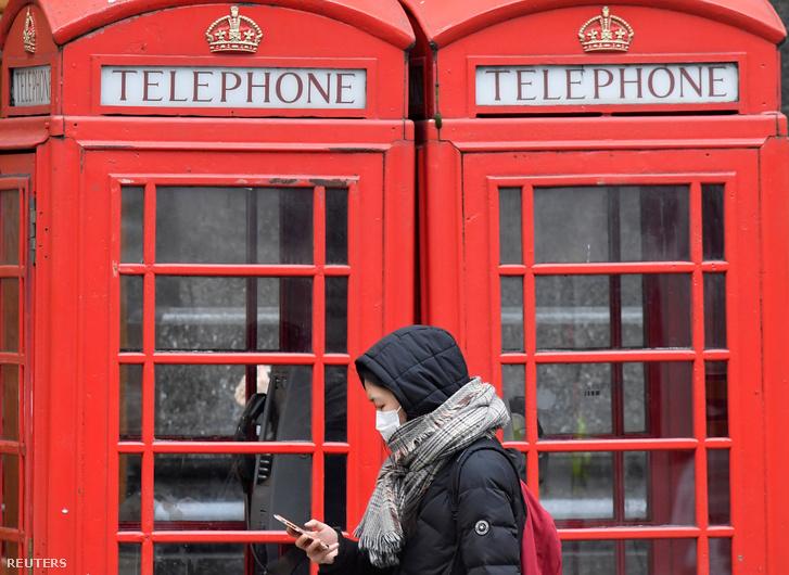 Nő sétál a londoni telefonfülkék előtt maszkban a koronavírus miatt 2020. március 15-én