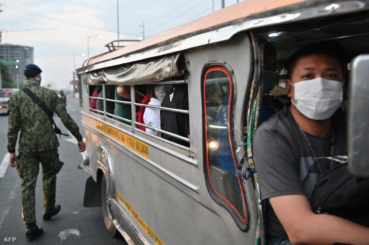 Egy fülöp-szigeteki rendőr 2020 március 15-én ellenőrzi az utasokat Manilában