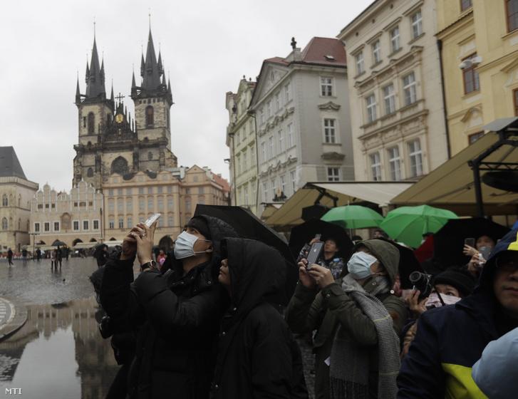 Védőmaszkot viselő emberek fényképeznek Prága óvárosában