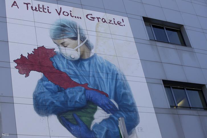 Franco Rivolli velencei illusztrátor felnagyított alkotása, amin egy orvos látható angyalszárnyakkal a hátán, karjában Olaszországgal egy bergamói kórház falán 2020. március 16-án