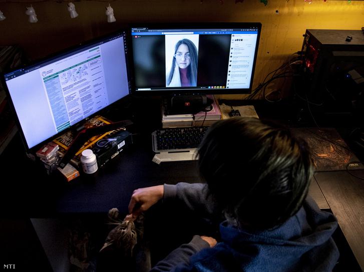 Egy budapesti gimnazista az otthonából internetkapcsolaton keresztül figyeli osztályfőnökének online tartott óráját 2020. március 16-án