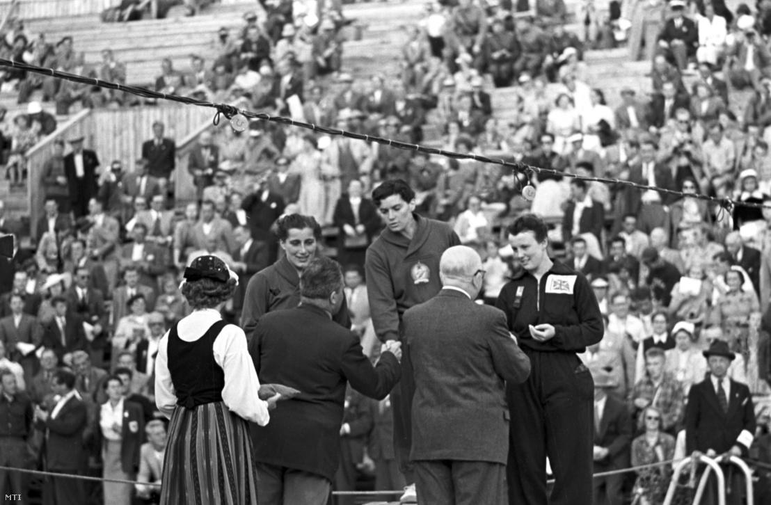 Székely Éva (k) úszó átveszi az aranyérmet a 200 m-es mellúszás versenyszám eredményhirdetésén a helsinki nyári olimpián. Mellette a dobogón az ezüstérmes Novák Éva (b) és a bronzérmes Helen Orr Gordon-McKay (brit).