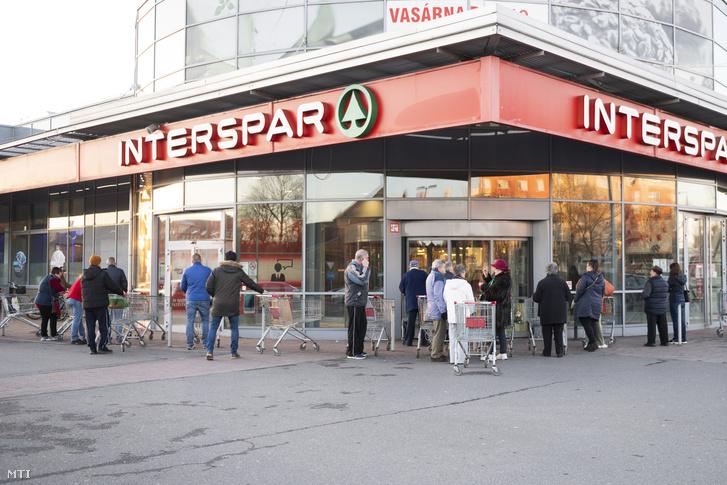 Vásárlók várakoznak már a nyitás előtt egy élelmiszerüzletnél Nyíregyházán 2020. március 14-én.
