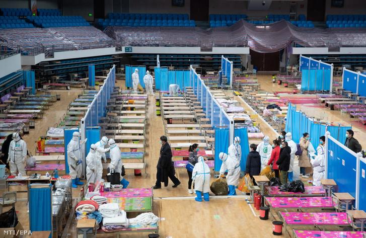 Gyógyultan elbocsátott páciensek és egészségügyi dolgozók távoznak az eddig szükségkórházként működő vuhani Hongsan sportcsarnokból 2020. március 10-én.