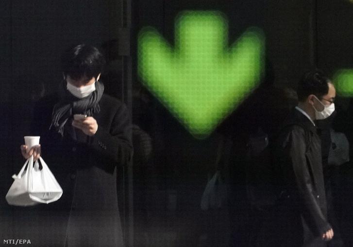 Járókelők a tokiói tőzsde kijelzője előtt
