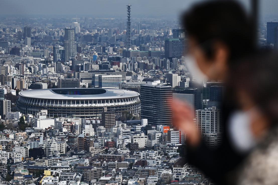 Arcmaszkot viselő emberek Tokióban, a háttérben a nyári olimpiai játékok fő helyszíne, az Új Nemzeti Stadion épülete 2020. március 9-én