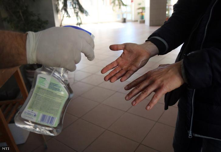 Fertőtlenítő folyadékot permeteznek egy az iskolába most érkező tanár kezére a bezárt Miskolci Herman Ottó Gimnáziumban 2020. március 16-án.