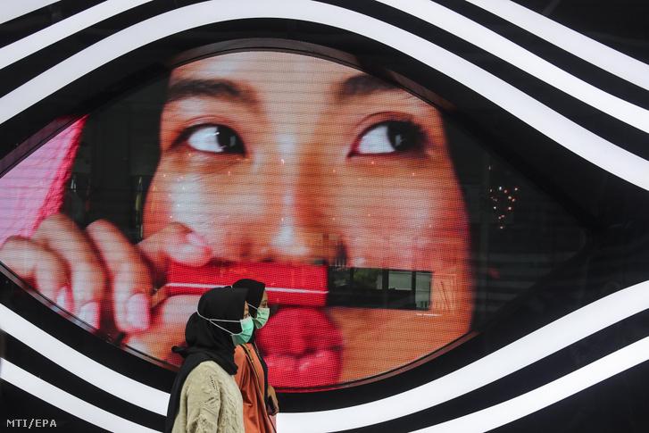 A koronavírus elleni védekezésül szájmaszkot viselő nők sétálnak egy óriásplakát előtt Kuala Lumpurban 2020. február 18-án