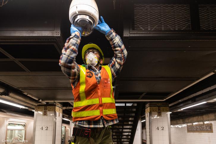 Munkás szerel védőmaszkban egy biztonsági kamerát a New yorki metróban 2020 március 12-én.
