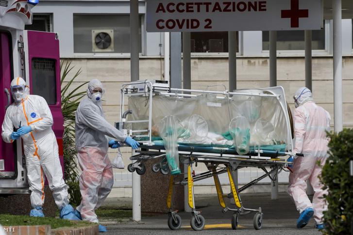 Biológiai szigetelősátorban szállítanak egy beteget a mentőautóból a római Gemelli kórház Columbus egységébe 2020. március 17-én.