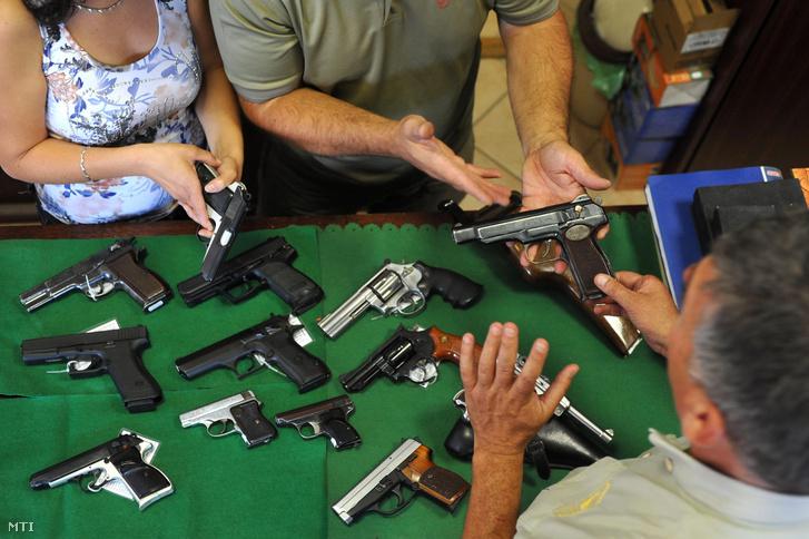 Önvédelmi fegyvereket mutatnak az eladók egy érdeklődőknek egy hatvani vadászboltban.