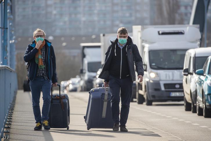 Arcmaszkot viselő férfiak gyalogolnak bőröndjeikkel a feltorlódott kocsisorok mellett a német-lengyel határon, a Frankfrut és Slubice városok közötti átkelőnél 2020. március 18-án
