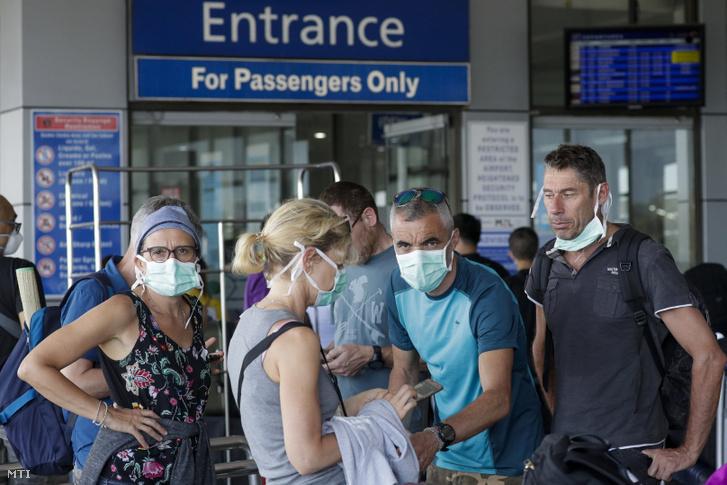 Indulásra készülő utasok a manilai Ninoy Aquino Nemzetközi Repülőtéren 2020. március 18-án.