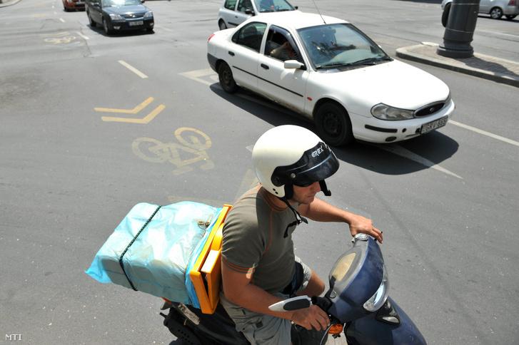 Képünk illusztráció! Egy motoros futár halad az Astoriánál.