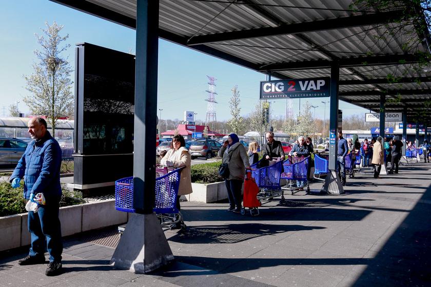 Kígyózó sorokban álltak az emberek a boltok előtt a belgiumi Drogenbosban a kijárásra vonatkozó korlátozások elrendelésének másnapján.