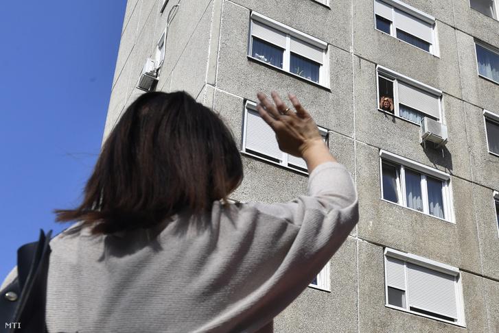 A koronavírus-járvány miatt messziről integetnek az ablakban álló idős hozzátartozójuknak családtagjai egy budapesti lakóháznál 2020. március 19-én.