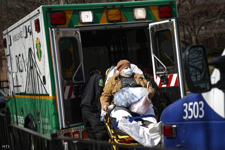 Védőmaszkos beteget tesznek mentőautóba a New York-i Brooklyn Kórházközpontnál 2020. március 18-án