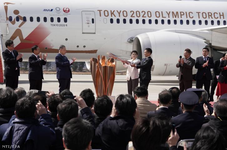 Nomura Tadahiro japán olimpiai cselgáncsbajnok (b5) és Josida Szaori olimpiai birkozóbajnok (b4) meggyújt egy kandellábert az ünnepségen amellyel a 2020-as tokiói nyári olimpiára Japánba érkező lángot fogadják a japán légierő higasimacusimai támaszpontján 2020. március 20-án.