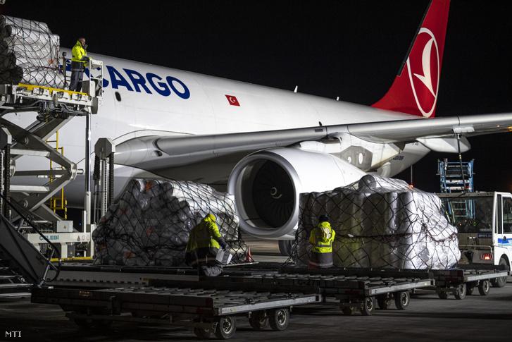 Kipakolják a Turkish Cargo Airbus A330 teherszállító repülőgépének rakományát, a török Teknomelt műszaki textilgyár védőmaszkokhoz szükséges alapanyagát a Liszt Ferenc-repülőtéren 2020. március 22-én