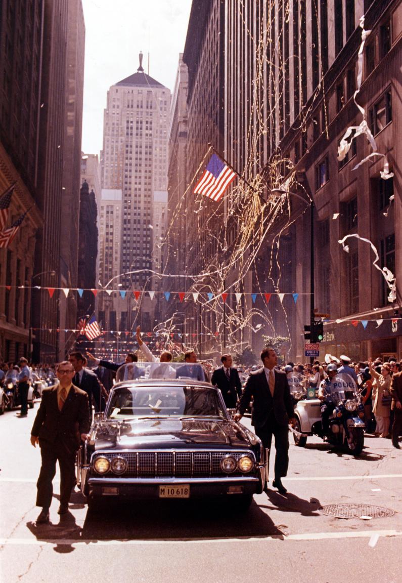 Ünnepi parádé New York-ban, a sikeres Holdküldetésről visszatérő űrhajósok tiszteletére. Középen fehér öltönyben Worden integet a lakosságnak.