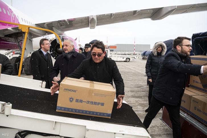 Gondos Miklós, Merkely Béla és Schanda Tamás segít a Wizz Air Sanghajból érkezett repülőgép szállítmányának kipakolásában a Liszt Ferenc-repülőtéren 2020. március 23-án.
