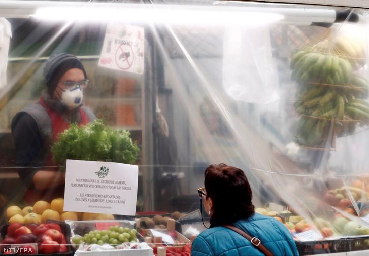 Műanyag védősátor alól szolgálja ki vásárlóit egy zöldség-gyümölcs kereskedő Pamplonában 2020. március 18-án.
