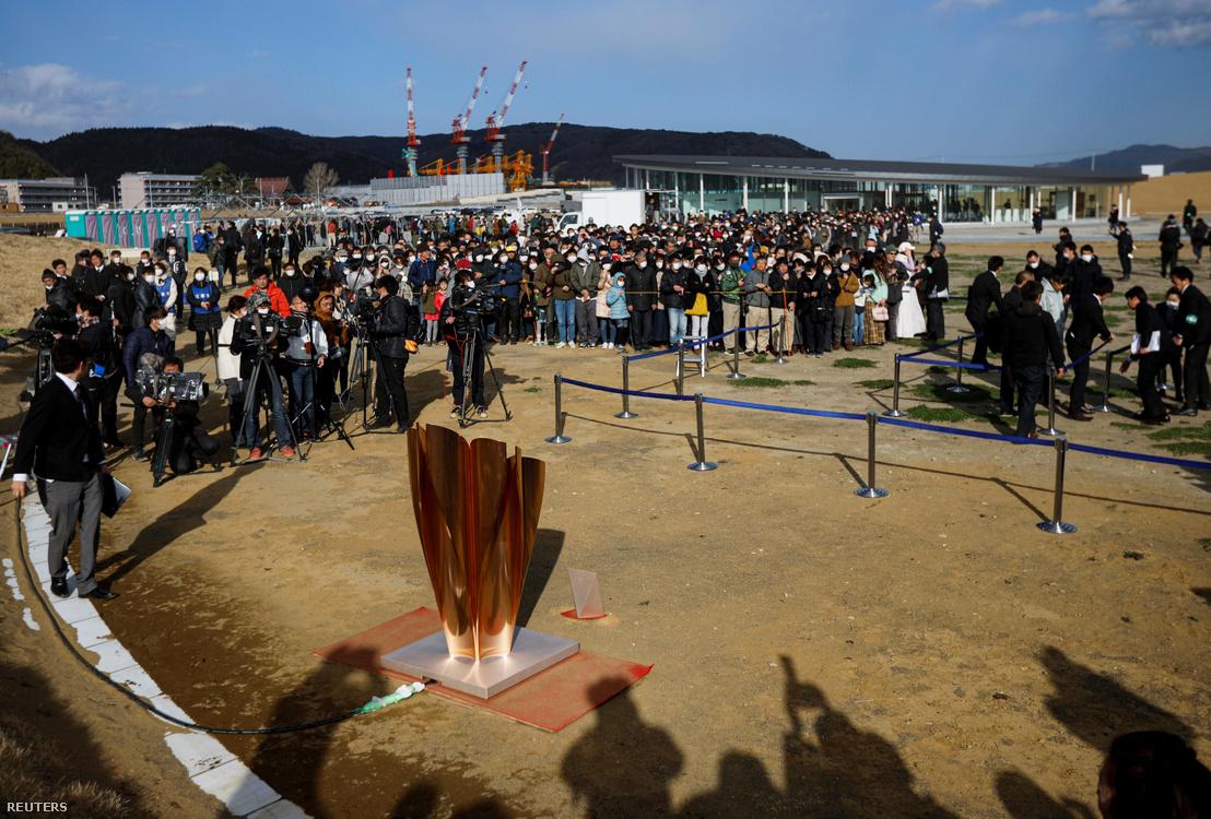 A COVID-19 koronavírus miatt maszkokban figyelik az emberek az olimpiai lángot az Ishinomaki Minamihama cunami helyreállítási emlékparkban 2020. március 20-án