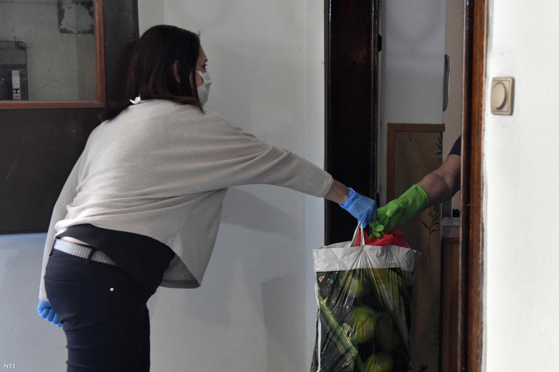 A koronavírus-járvány miatt védőmaszkot és gumikesztyűt viselő nő élelmiszercsomagot ad be az ajtóban idős hozzátartozójához egy budapesti lakóházban 2020. március 19-én.