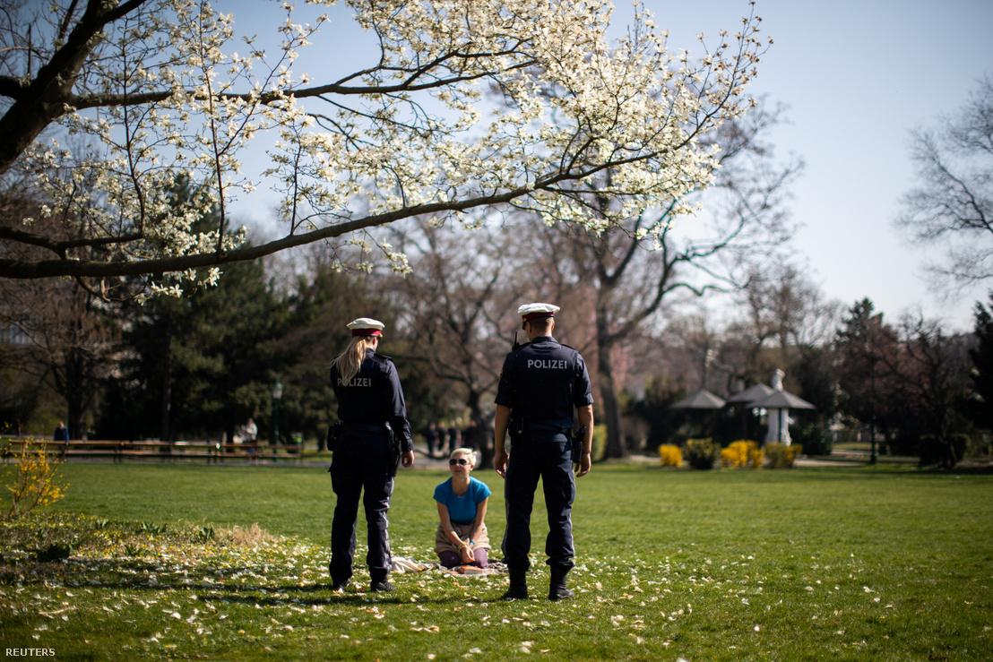 Rendőrök beszélnek egy helyi lakossal a bécsi Stadtparkban 2020. március 20-án.