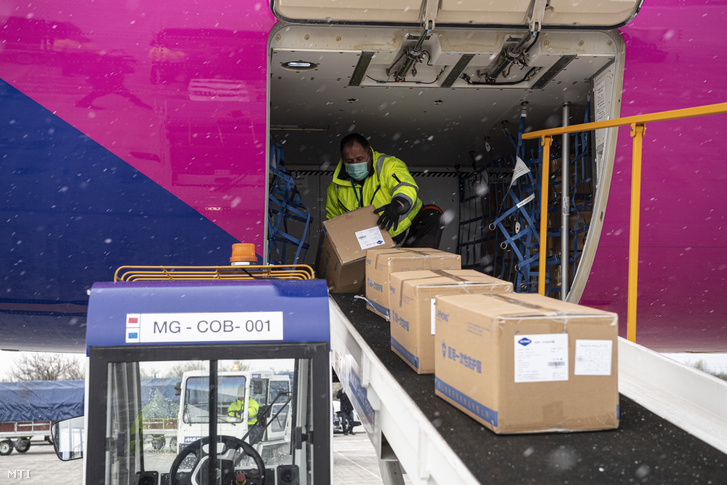 Kipakolják a Wizz Air Sanghajból érkezett repülõgépének szállítmányát a Liszt Ferenc-repülőtéren 2020. március 23-án. A gép a koronavírus elleni védekezéshez használható védőruhából harmincezret, orvosi védőmaszkból nyolcvankétezret hozott.