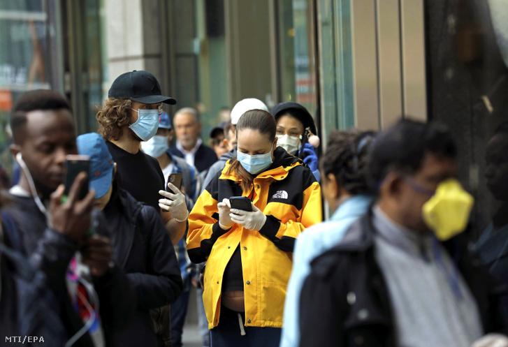Az új koronavírus járványa miatt védõmaszkban várakoznak vásárlók egy New York-i élelmiszerüzlet előtt New Yorkban 2020. március 20-án.