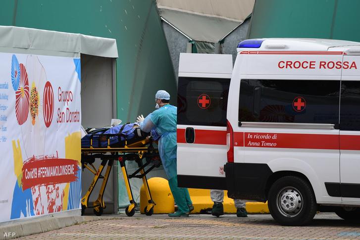 Egészségügyi dolgozók fogadnak egy koronavírussal fertőzött beteget a milánói San Raffaele kórház melletti sportközpontban létrehozott intenzív osztályon 2020. március 23-án.