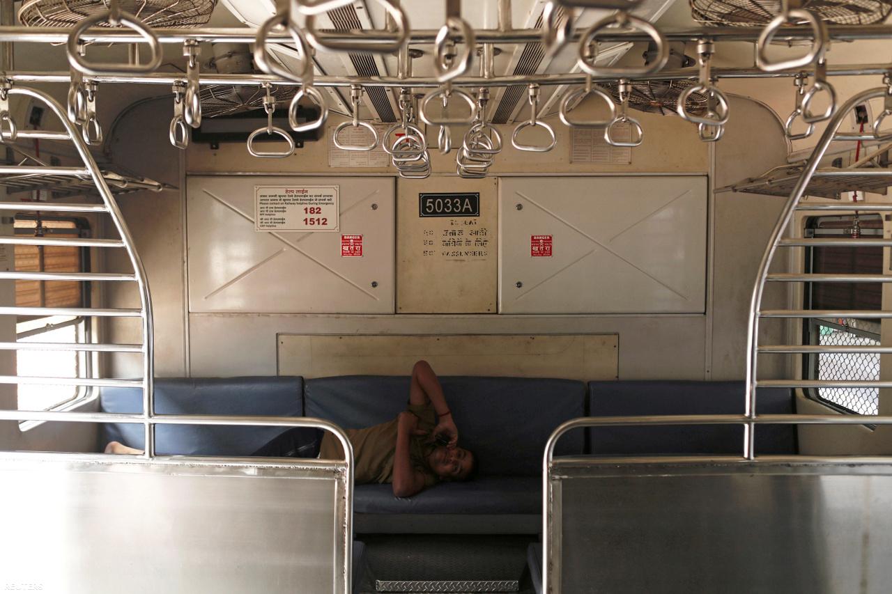 Vasúti dolgozó telefonál egy üres vasúti fülkében az indiai Mumbaiban március 23-án, miután leállították a vonatközlekedést a koronavírus terjedésének lelassítása érdekében.
