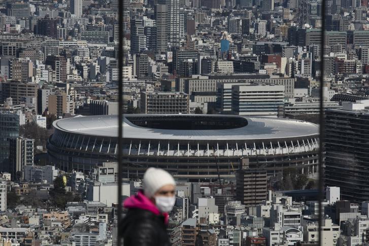 Egészségügyi maszkot viselő turista a tokiói Sibuja felhőkarcoló kilátójában az olimpiai játékok nyitó- és záróünnepségének otthont adó stadion előterében