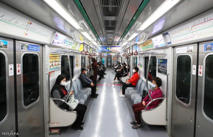 Egymástól kellő távolságot tartva utaznak a metrón az új típusú koronavírus terjedése miatt védőmaszkot viselő utasok Szöulban 2020. március 23-án.