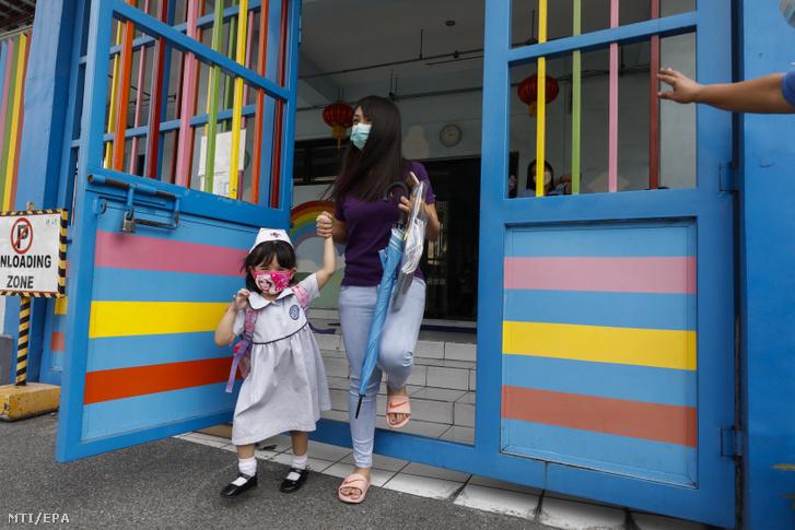 Légzőmaszkot visel egy óvodás lány és anyja a koronavírus terjedése elleni óvintézkedésként a Fülöp-szigeteki Quezon nagyvárosban 2020. január 29-én.