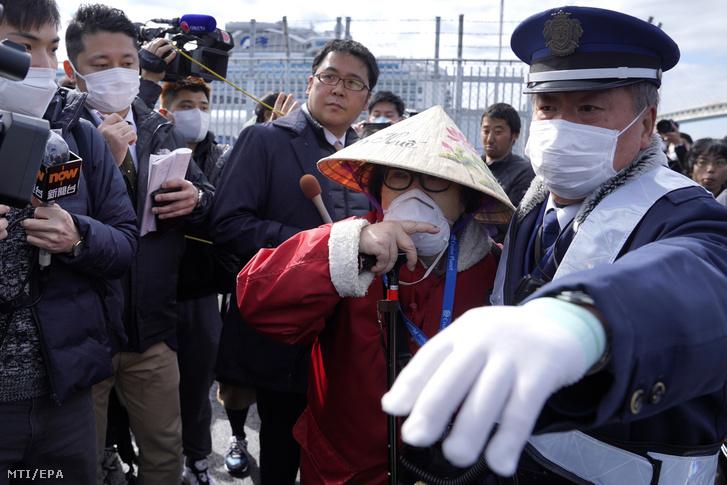 A jokohamai kikötőben karantén alá vont Diamond Princess amerikai óceánjáró egyik utasa a 14 napos karantént követően elhagyja a kikötőt 2020. február 19-én.