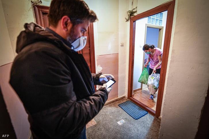 Egy román civil szervezet segítője visz élelmiszert a járvány miatt bukaresti otthonába szorult fiatal anyának 2020. március 15-én