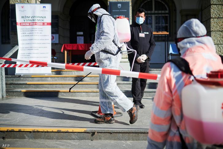 Védőruházatba öltözött munkások fertőtlenítik az utcát a városháza előtt a szlovéniai Kranjban 2020. március 23-án
