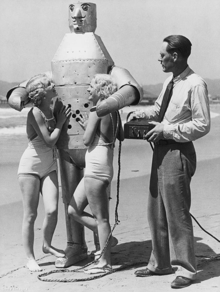 Döbbenet, de ez a kép Machtéról, a mechanikus férfiról 1931-es! A robotot feltalálója éppen távirányítja a képen és Machténak több se kell, kettesével szedi éppen fel a nőket Venice Beachen!